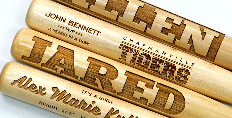 Personalized engraved miniature wooden bats.