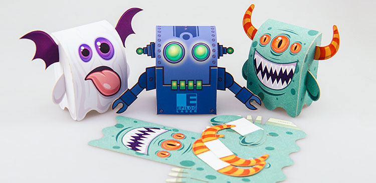 A group of three paper monsters cut out with an Epilog Laser machine
