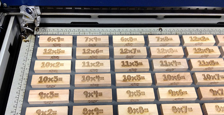 A jig full of laser engraved Jenga pieces