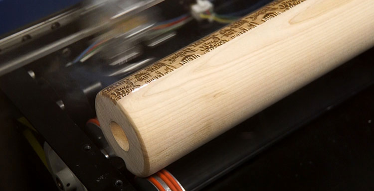 Laser engraving a wooden rolling pin.