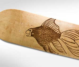 Skateboard engraved with a 3D fish design.