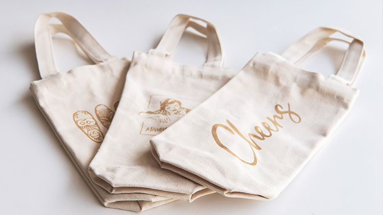 group of laser engraved canvas wine bags