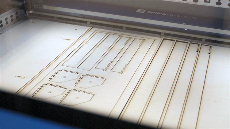 A laser-cut sheet of plywood in an Epilog Laser machine.