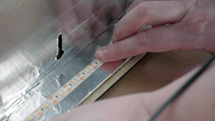 Applying adhesive LED light strip to the interior sides of the box.