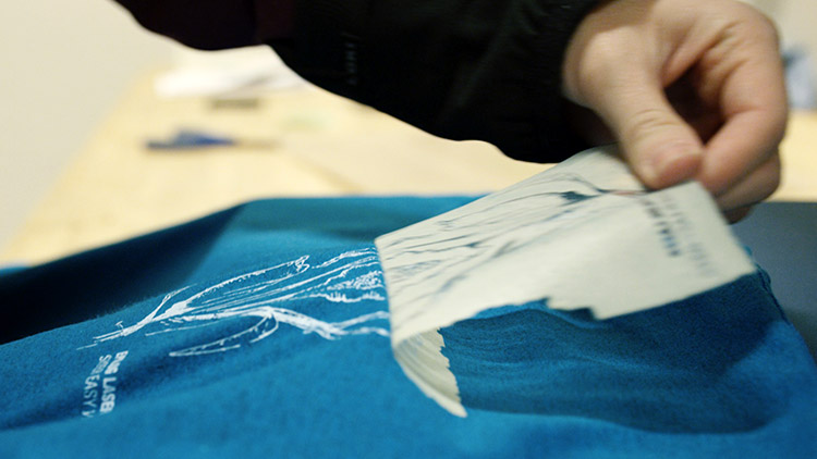 Peeling away the heat transfer material to reveal the heat-pressed design