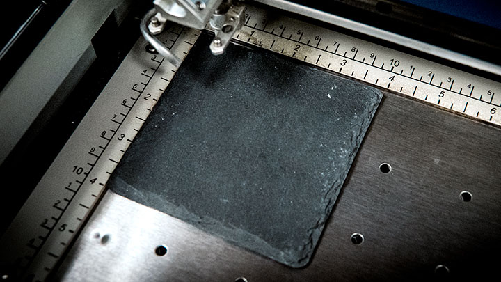 slate coaster placed in the laser system