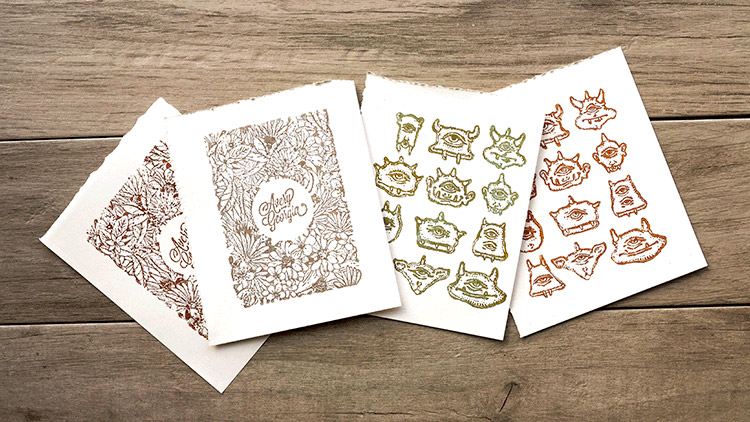 A spread of four prints made from laser engraved wooden stamps.